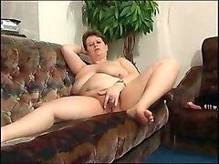 bbw mature white woman on the couch fingers her shaved pussy