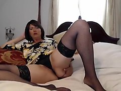 Brunette MILF spreads her stockinged thighs in bed to play