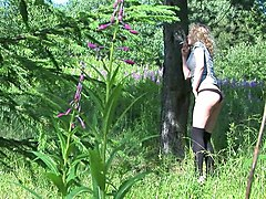 blonde amateur curly haired chick in the forest pisses under the tree